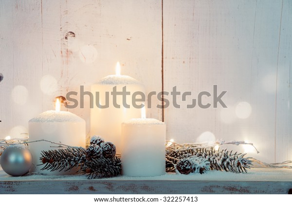Christmas candles and snowy fir branches over white wooden background with lights