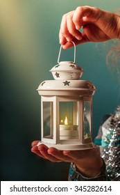 Christmas candlestick with burning candles in the hands of a child