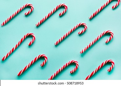 Christmas candy cane lied evenly in row on blue background. Flat lay and top view