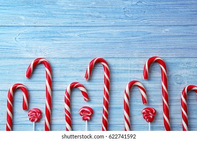 Christmas candy canes and lollipops on wooden background
