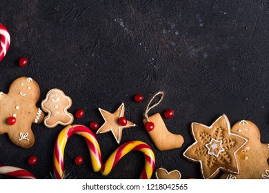 Christmas canes and traditional cookies for the new year on the black background with a copy space