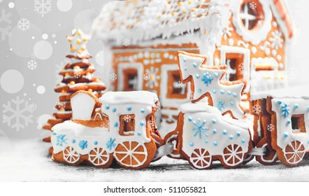 Christmas card. Assorted Christmas gingerbread cookies. Christmas gingerbread village, house, train, tree. Christmas New Year's background with snowflakes. Christmas food gingerbread house, train