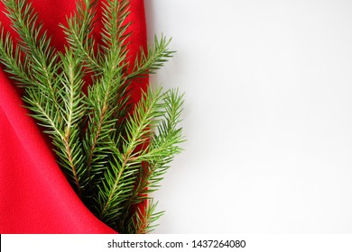 Christmas card background. New year holiday. Christmas still life. The view from the top. Free space for text. Green pine branches on a red background. Creative composition for greeting, poster.
