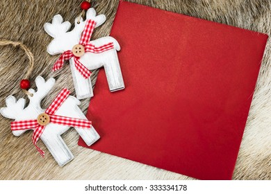 Christmas card background with red envelope and two white wooden reindeer ornaments on a natural skin of reindeer. Space for text.