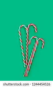 Christmas card or banner with candy sweets and gift box over the dark green background. top view, copy space, holiday concept, Christmas background