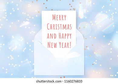 Christmas card in blue envelope on blue background decorated with confetti. Holiday and invitation mockup.