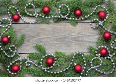 Christmas card concept with fir tree branches, red baubles and silver bead chain on wooden background - text space