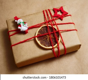 Christmas card for congratulations. brown gift box wrapped in brown craft paper with dry lemon slices, present box on a white snowdrift background with place for text. snowman on red pin.