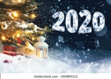 Christmas card - gifts and a lantern in the snow under a Christmas tree decorated with lights and Christmas decorations, and inscription 2020