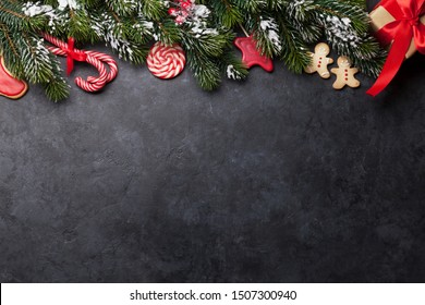 Christmas card with gingerbread cookies and fir tree branch covered by snow on stone background. Top view with space for your greetings