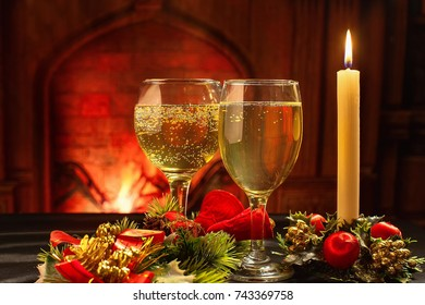 Christmas card, a glass of champagne and Christmas candle on the background of the fireplace