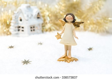 Christmas card in gold colour: ceramic girl-angel with snow-covered house