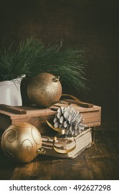 christmas card with golden baubles, cones and fur tree on wooden background