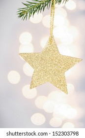 Christmas card with golden star and tree  branch on Defocused Christmas Bokeh silver bright background