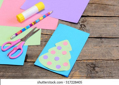 Christmas card guide. Step. Paper Christmas greeting card, pencil, glue stick, colored paper, scissors on wood background. Children paper art at home, in kindergarten. Christmas craft for preschooler
