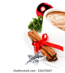 Christmas card with hot cup of cappuccino,  cinnamon sticks and christmas tree branch isolated, closeup