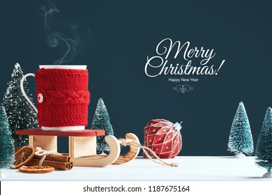 Christmas card with the inscription Merry Christmas. White cup with hot cocoa in red knitted clothes on Santa Claus sleigh on a dark background with a toy tree, a red bowl, cinnamon sticks and slice