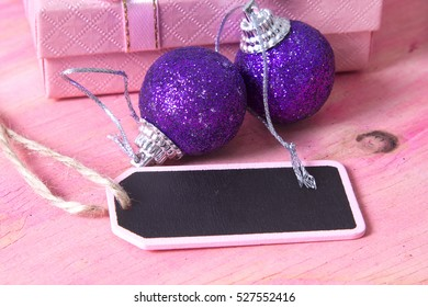 Christmas card with label, gift box and Christmas balls on pink background
