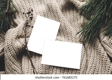 christmas card mockup. empty christmas card with space for text, template on knitted sweater and fir branches. flat lay, merry christmas, seasonal greetings, happy holidays. atmospheric  moments