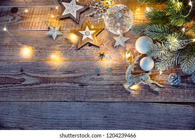 Christmas card at old vintage board with gold deer branch christmas tree wooden stars and white balls.
