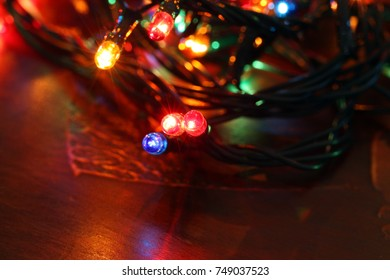 christmas card, pattern: glowing border of colorful christmas lights over golden background with copy space, decorative garland
