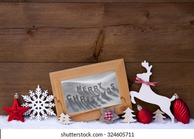 Christmas Card With Picture Frame On Snow. Englisch Text Merry Christmas. Red Christmas Decoration Like Christmas Ball, Snowflake, Tree, Star And Reindeer. Wooden And Vintage Background