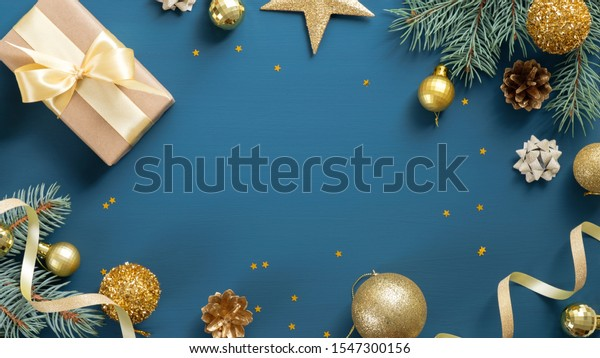 Christmas card with pine tree branches, gifts, golden decorations over blue background. Flat lay, top view, copy space. Christmas frame, New year banner mockup