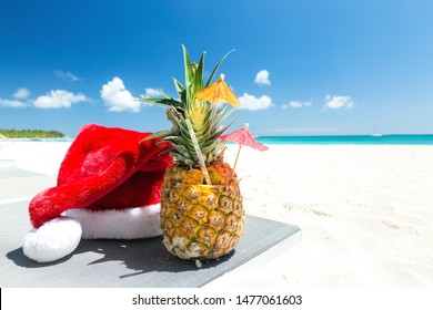 Christmas card with pineapple cocktail on sandy caribbean beach background. New Year holiday at summer vacation getaway, banner with copy space for your text