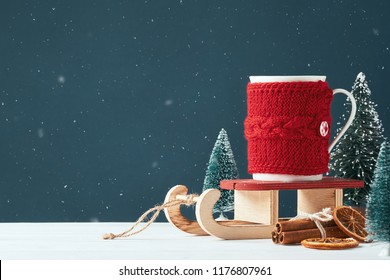 Christmas card with place for your text. White cup for cocoa warmed red knitted clothes on a sled of Santa Claus on a dark background with toy Christmas trees in the background. Snowfall