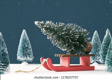Christmas card with place for your text. A bright Christmas tree toy in the form of a fir tree on a Santa Claus sleigh on a dark background with toy Christmas trees in the background. Snowing