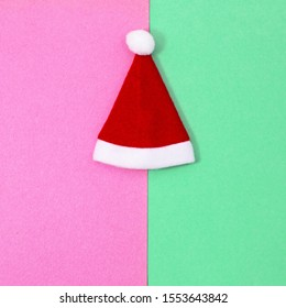 Christmas card with Red Santa hat on neo mint green pink background, flat lay. Pop Art Design, Minimal Creative pop-art style. Merry Christmas and New Year Happy Holidays.