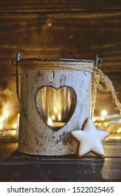 Christmas card. Small lantern with heart and cinnamon star on wooden background