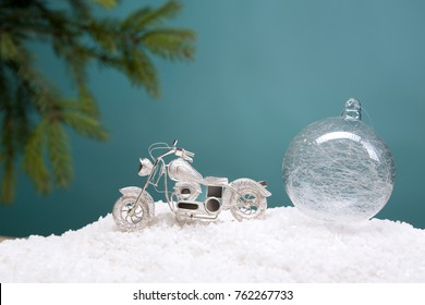 Christmas card. A small motorcycle in the snow. New Year's greeting card, close-up. Congratulation for a motorcyclist. Christmas toys and decor. christmas tree branch