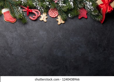 Christmas card with sweets, gift box and fir tree branch on stone background. Top view backdrop with space for your greetings. Flat lay
