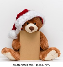 Christmas card with Teddy Bear  With a gift and holiday decoration. Christmas Teddy bear holding a place for text and other Christmas decor.