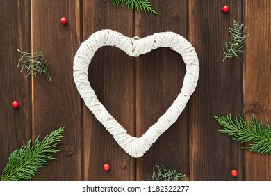 Christmas card, Valentine's day with place for your text. Large white heart shape on a background of brown old wooden boards framed by green branches of spruce, red bead