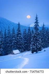 Christmas card with a winter landscape. A fabulous view with light in the window of a wooden house and a path in the snow. Full moon in the mountains
