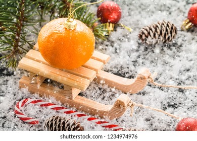 Christmas card with wooden sled, with fresh tangerine over old wooden background. image with selective focus