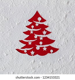 Christmas card with xmas tree drawing in flour on red table - copy space on nice textured white
