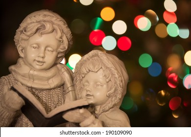 Christmas Carolers - statue of Christmas carolers / singers in front of Christmas tree with out of focus background.