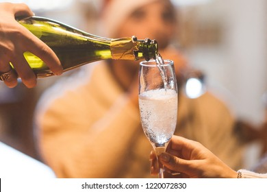 Christmas celebration with champagne - group of friends drinking and toasting together - a hand with bottle pouring sparkling wine in a glass (flute)