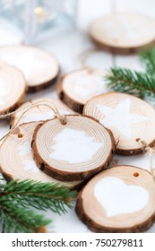 Christmas celebration concept. Self made festive decorations made of wood slices and white painted ornaments