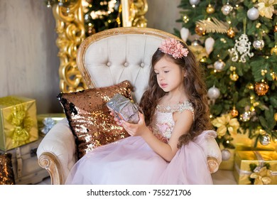 Christmas celebration. Cute little girl in a beautiful dress sitting near the Christmas tree. Christmas miracles. Luxurious Christmas decoration