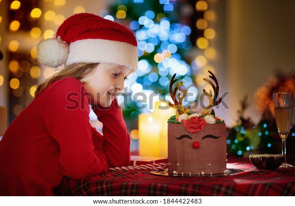 Christmas celebration at home. Little girl with reindeer Xmas cake. Baking dessert and cooking in holiday season. Kids bake cookies. Child eating gingerbread pastry. Family at Christmas tree.
