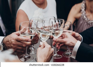 christmas celebration. people toasting with champagne and wine glasses in hands clinking at luxury wedding reception at restaurant. cheering. luxury life concept. space for text.