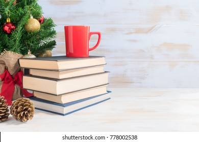 Christmas celebration with red cup on books against white wooden background.
