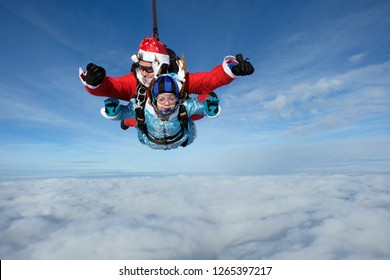 Christmas celebration and tandem jump. Santa Claus is flying in the sky with child.