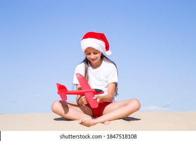 Christmas celebration vacations on a tropical beach: Happy cute little girl wearing a red Santa hat sitting on the sandy beach by the sea and holding a red toy plane on her hands on clear sunny day