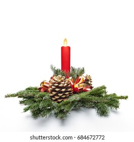 Christmas centerpiece decoration with a red color candle lit and fir tree leaves. White background.