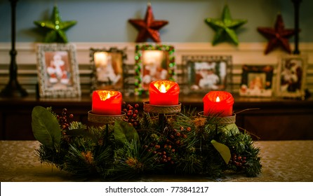 Christmas centerpiece with three red candles lit and blurred background with colorful stars.